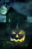 在一个鬼的房子前面的万圣节南瓜 免版税库存图片