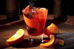 在一个鸡尾酒杯的鸡尾酒Americano在一个木立场 免版税库存图片