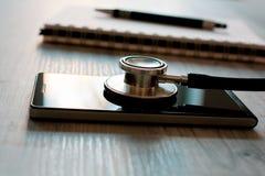 在一个黑智能手机的听诊器在笔记薄和圆珠笔-固定旁边一个残破的手机概念 库存图片