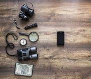 在一个黑暗的木背景护照地图照相机放大器灯笼指南针上双筒望远镜给智能手机旅行假期打电话 免版税库存图片
