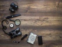 在一个黑暗的木背景护照地图照相机放大器灯笼指南针上双筒望远镜给远足旅行假期的智能手机刀子打电话 库存图片