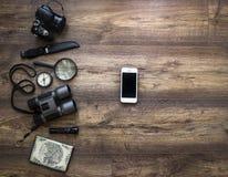 在一个黑暗的木背景护照地图照相机放大器灯笼指南针上双筒望远镜给远足旅行假期的智能手机刀子打电话 免版税库存照片