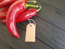 在一个黑木标记的红辣椒 免版税库存照片