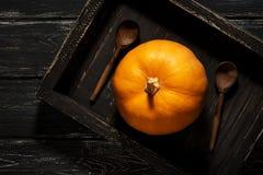 在一个黑木盘子的一个小南瓜有在一个土气样式的木匙子的 在视图之上 库存照片