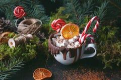 在一个黑杯子的圣诞节热巧克力用焦糖的桔子、冷杉分支和棒棒糖在黑暗的背景,选择聚焦 免版税库存照片