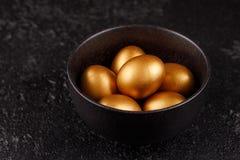 在一个黑杯子的金黄鸡蛋在黑织地不很细背景 复活节彩蛋 鸡蛋,绘在金子为假日 免版税库存照片
