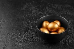 在一个黑杯子的金黄鸡蛋在黑织地不很细背景 复活节彩蛋 鸡蛋,绘在金子为假日 库存照片