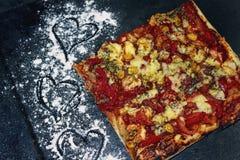 在一个黑煎锅的比萨切片 库存图片