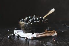 在一个黑玻璃碗的黑醋栗有在一块灰色餐巾的一个匙子身分的在黑木背景 图库摄影