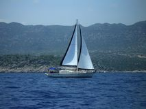 在一个黑白风帆下的一条白色游艇 图库摄影