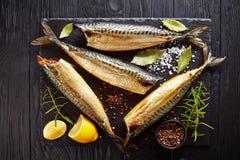 在一个黑盘子的热的熏制的鲭鱼 免版税库存照片