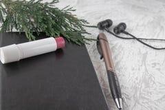 在一个黑笔记本的绿色枝杈在一副笔、唇膏和耳机旁边在白色背景 免版税库存图片