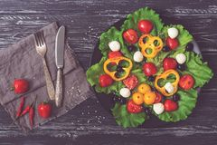 在一个黑色的盘子的希腊沙拉 在土气背景的沙拉与叉子和刀子 被定调子的照片 库存照片