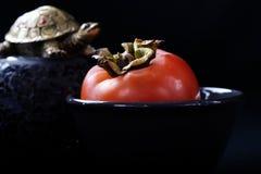 在一个黑色的盘子的成熟橙色柿子果子在黑背景,佛教标志,Chusok收获节日 库存照片