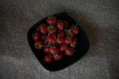 在一个黑色的盘子的有些草莓 免版税库存照片