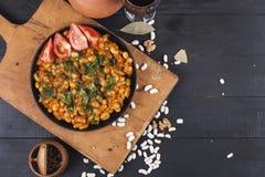 在一个黑色的盘子的煮熟的豆在木背景 免版税库存照片