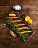 在一个黑色的盘子的阿根廷烤大虾在木背景 库存照片