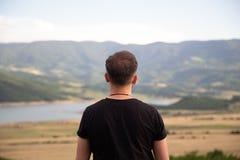 在一个黑T恤杉身分的在自然的男性在美好的领域前面和小山 库存照片