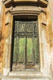 在一个经典大厦的老绿色破裂的木门 免版税库存图片