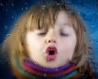 在一个满地露水的窗口后的小女孩 免版税库存照片