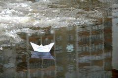 在一个水坑的纸小船在早期的春天 免版税库存照片
