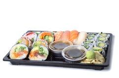 在一个黑塑料盘子的被分类的寿司卷 库存图片