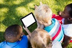 在一个晴天期间,使用技术的孩子 免版税库存照片