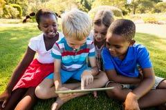 在一个晴天期间,使用技术的孩子 图库摄影