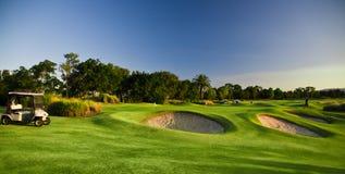 在一个晴天的高尔夫球场和购物车 库存照片