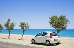 在一个离开的海滩旁边停放的汽车 免版税库存图片