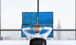 在一个贸易的驻地前面坐包括有财务数据的四个屏幕一位松弛贸易商的背面图 A 免版税库存照片