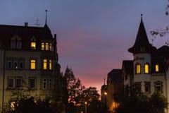在一个10月秋天晚上大厦、被照亮的窗口和stre 图库摄影