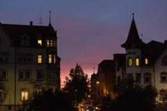 在一个10月秋天晚上大厦、被照亮的窗口和stre 免版税图库摄影