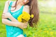 在一个晴朗的夏日走在庭院里的美丽的女孩和在手保留黄色蒲公英 库存图片