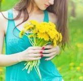 在一个晴朗的夏日走在庭院里的美丽的女孩和在手保留黄色蒲公英 库存照片
