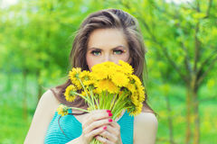 在一个晴朗的夏日走在庭院里的美丽的女孩和在手保留黄色蒲公英 免版税库存图片