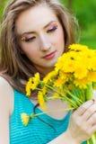 在一个晴朗的夏日走在庭院里的美丽的女孩和在手保留黄色蒲公英 免版税库存照片