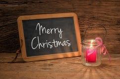 在一个黑板前面的蜡烛有文本的圣诞快乐 图库摄影