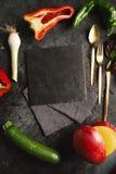 在一个黑板岩乳酪板附近的菜 库存照片