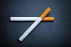 在一个黑板岩切板的两根香烟 定调子 免版税库存照片