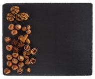 在一个黑板岩板的坚果混合 背景查出的白色 免版税库存照片