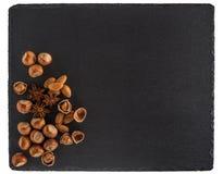 在一个黑板岩板的坚果混合 背景查出的白色 T 库存图片