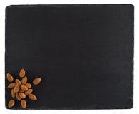 在一个黑板岩板的杏仁 背景查出的白色 免版税库存图片