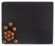 在一个黑板岩板的榛子 背景查出的白色 库存图片