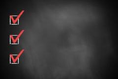 在一个黑黑板的三个红色明显的复选框 免版税图库摄影