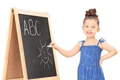 在一个黑板的女孩文字有白垩的 免版税图库摄影