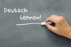 在一个黑板的手有德国人词的德意志lernen (学会 免版税库存图片