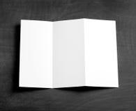 在一个黑黑板的空白的折叠的页小册子 图库摄影
