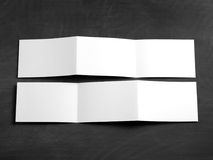 在一个黑黑板的空白的折叠的页小册子 免版税库存图片