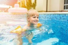 在一个水池的一点逗人喜爱的白肤金发的女孩游泳与,佩带的可膨胀的袖子 定调子 免版税库存图片